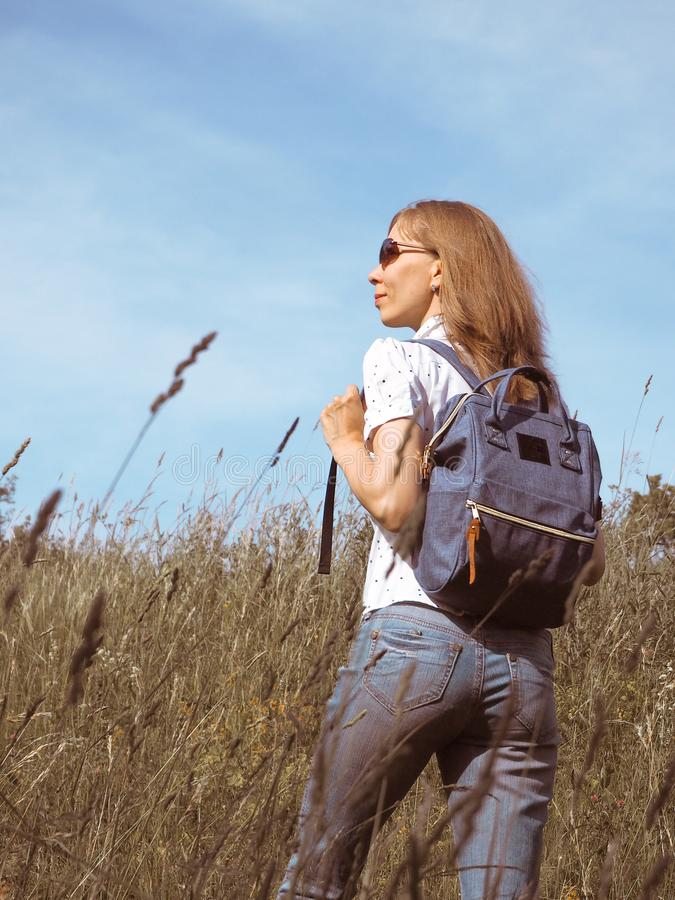 Flickahandelsresande som fotvandrar med ryggsäcken på alpina ängar Utomhus- semestrar för sommar för affärsföretag för lopplivsst royaltyfria foton