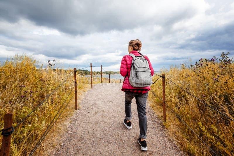 Flickahandelsresanden med en ryggsäck går runt om ön av Suomenl royaltyfri foto