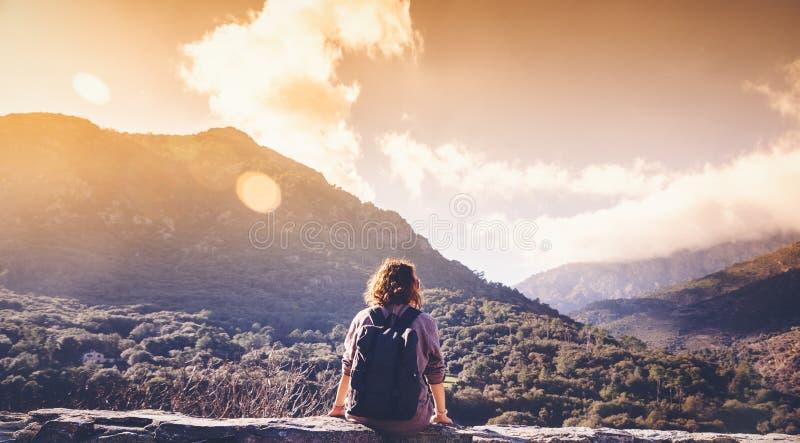 Flickahandelsresanden med en ryggsäck sitter förbise solnedgången och moen arkivbilder