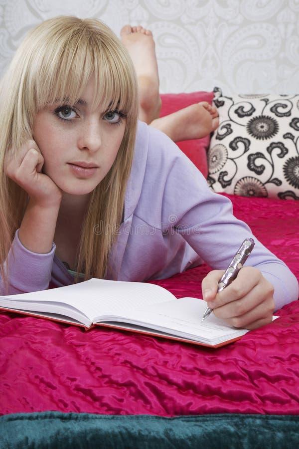 Flickahandstil på boken i säng arkivbild