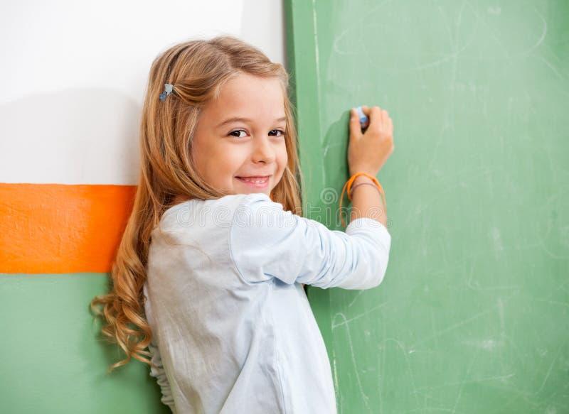 Flickahandstil på den gröna svart tavlan i klassrum arkivbild