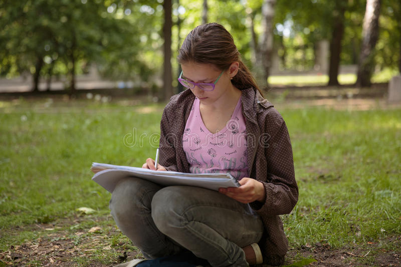 Flickahandstil på hennes anteckningsbok arkivfoton