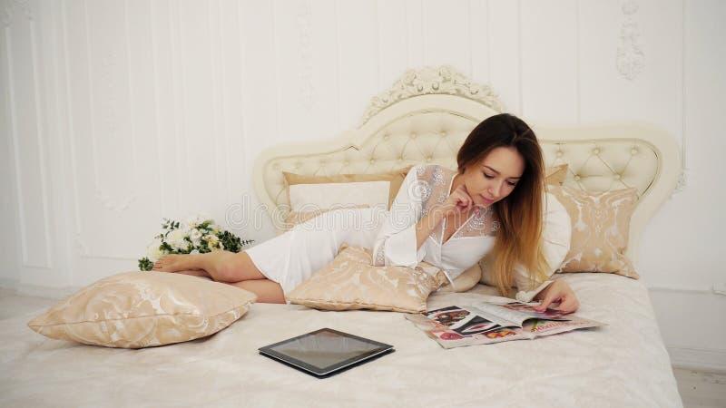 Flickahemmafru Leafing Through Magazine och blickrecept, lögner på säng i vit arkivfoton