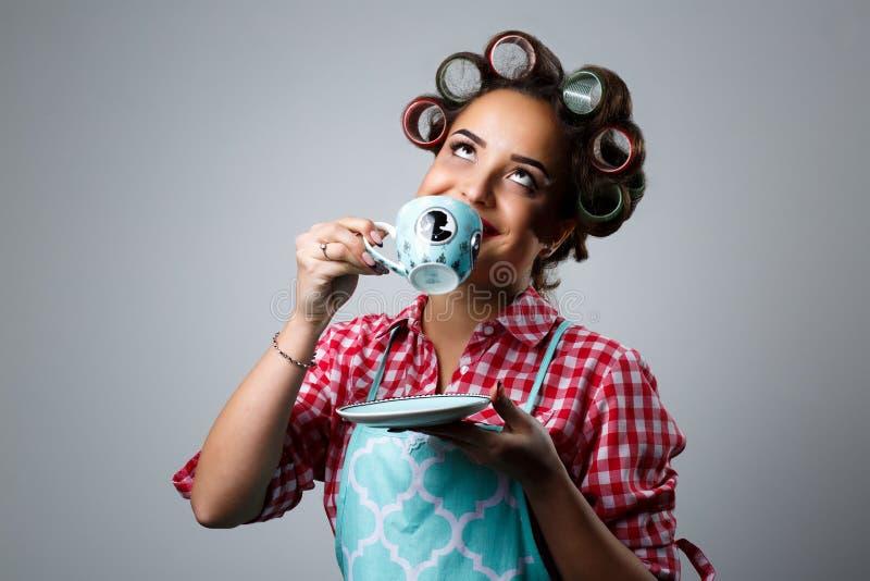 Flickahemmafrun dricker te från en kopp royaltyfria foton