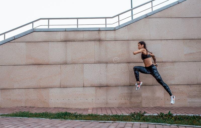 Flickaidrottsman nen hoppar, körningar för morgon joggar I sommaren i stad Begreppet av en sund livsstil Sikt från arkivfoto