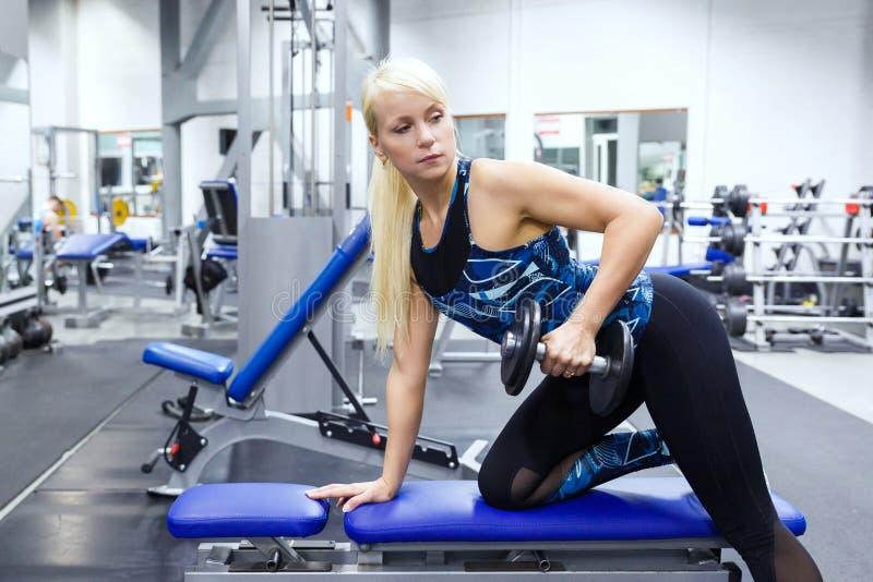 Flickaidrottsman nen utför en övning med hantlar i idrottshallen royaltyfri bild