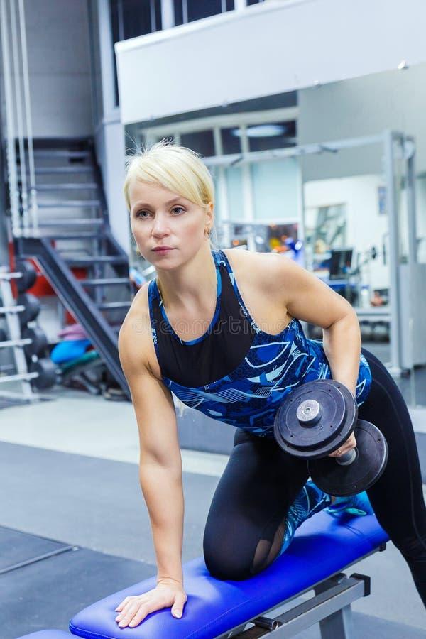 Flickaidrottsman nen utför en övning med hantlar i idrottshallen Vertikalt foto arkivbild