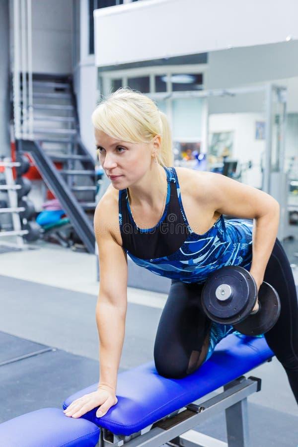 Flickaidrottsman nen utför en övning med hantlar i idrottshallen Vertikalt foto fotografering för bildbyråer