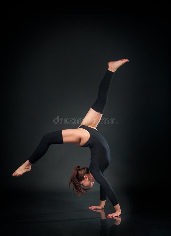 Flickaidrottsman nengymnast som utför akrobatiska beståndsdelar som hoppar på a arkivbild