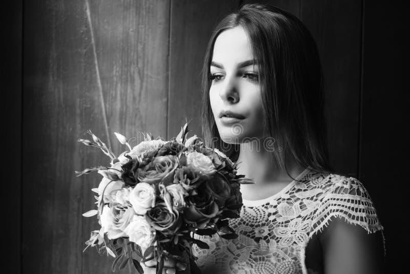 Flickainnehavet blommar i händer, brud i den hållande bröllopbuketten för den vita klänningen, bukett av bruden från roskrämsprej arkivfoton