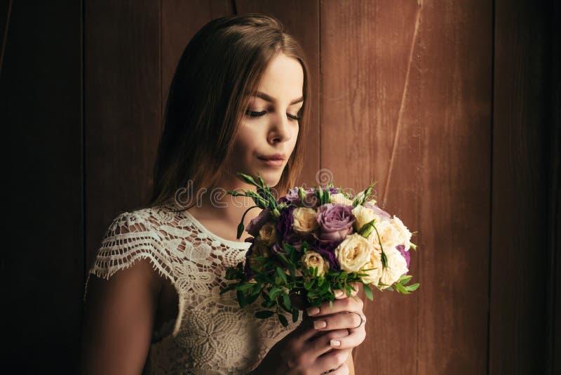Flickainnehavet blommar i händer, ung härlig brud i den vita dren royaltyfri foto