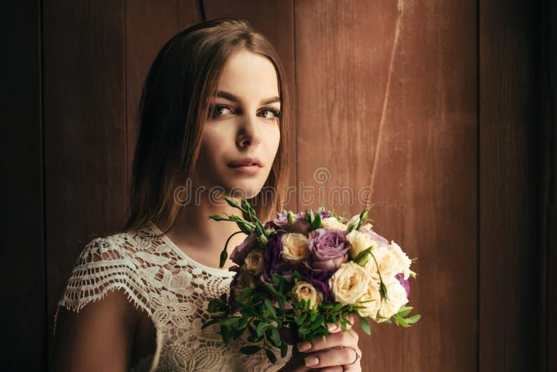 Flickainnehavet blommar i händer, ung härlig brud i den vita dren arkivfoton