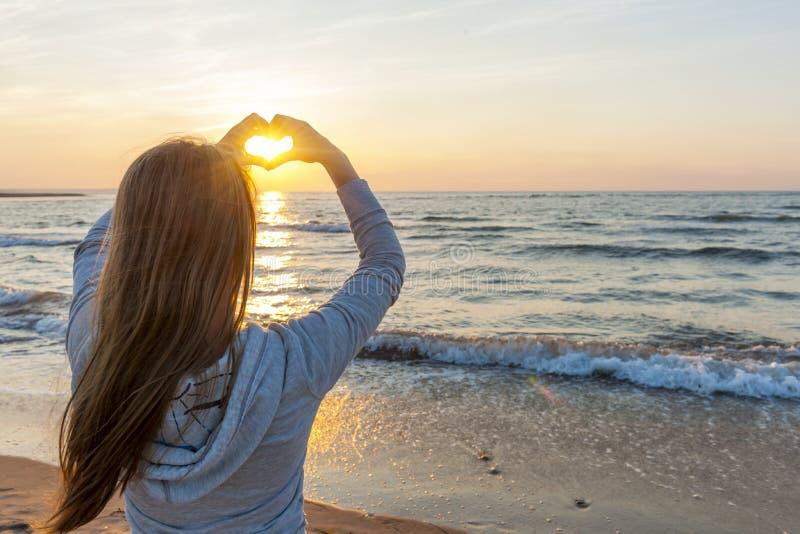 Flickainnehavhänder i hjärta formar på stranden royaltyfri fotografi