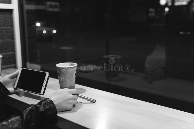 Flickainnehavsmartphonen i hand, sitter i kaf?t, arbete, pennan, bruksgrej N?tverk wifi, samkv?m, kommunikation Freelancerarbeten fotografering för bildbyråer
