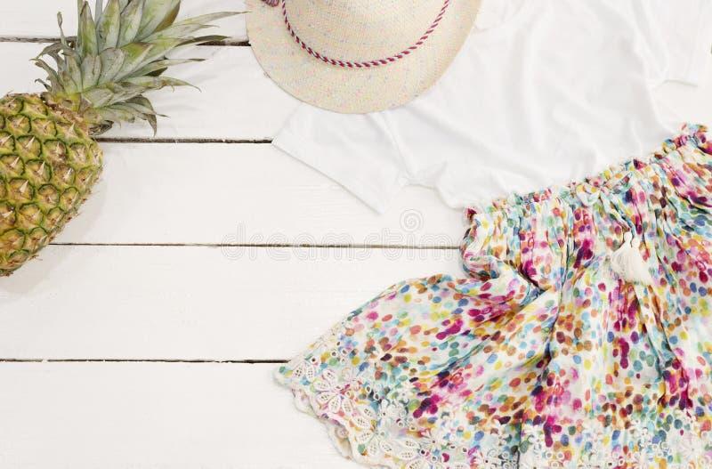Flickakläder- och tillbehörcollage Sugrörhatt, blom- klänning, ananas Vit gammal träbakgrund arkivfoton
