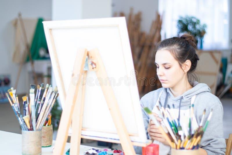 Flickakonstnären målar en bild på kanfas royaltyfri foto