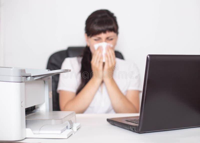 Flickakontorsarbetaren sitter på en dator i kontoret och blåser hennes näsa begreppet av allergier för att torka och fuktig luft  arkivbilder