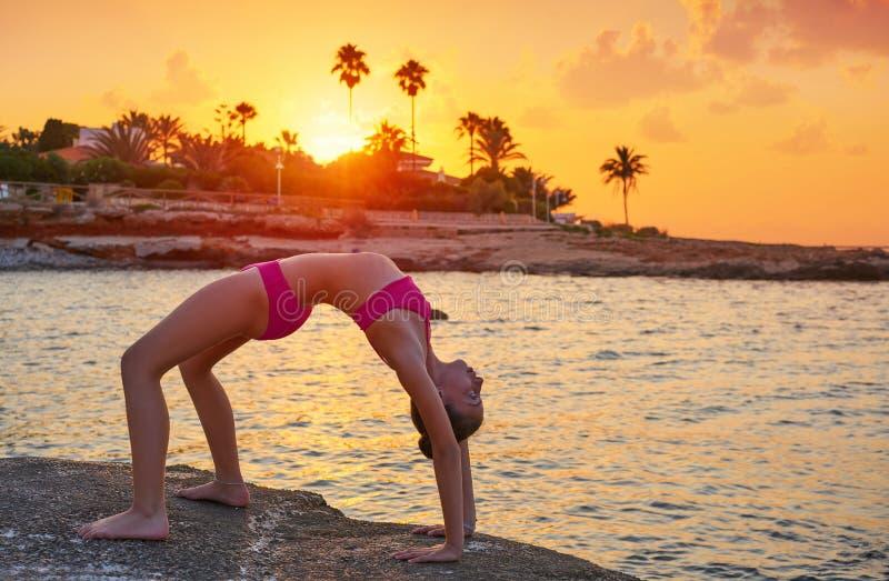 Flickakontur på strandsolnedgånggymnastik royaltyfri fotografi