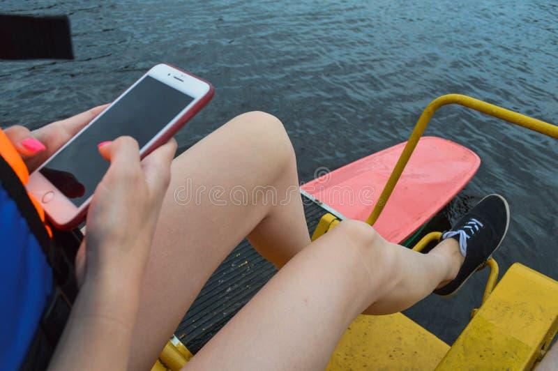 Flickakvinnan vrider hennes fot på pedalerna av en simma sportlätthet av ett katamaranfartyg och använder en mobiltelefon med ett royaltyfri bild