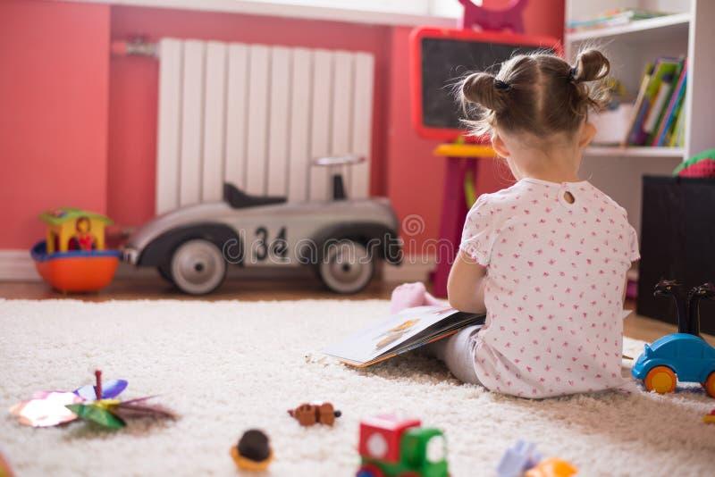 Flickaläsebok i barnrummet arkivfoton