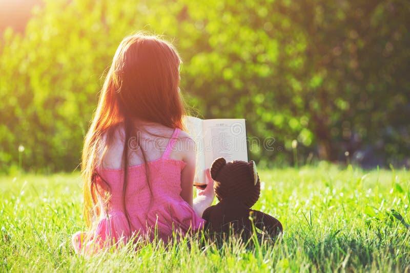 Flickaläsebok med leksaken för nallebjörn arkivbild