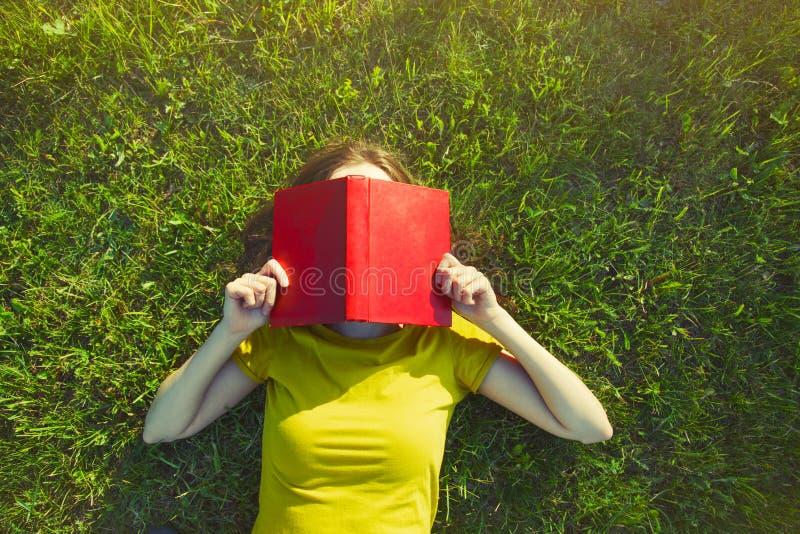 Flickaläsebok som ligger i gräs fotografering för bildbyråer