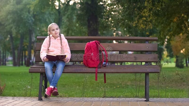 Flickaläseboken och att sitta på bänk parkerar in och att göra läxa utomhus, studien fotografering för bildbyråer