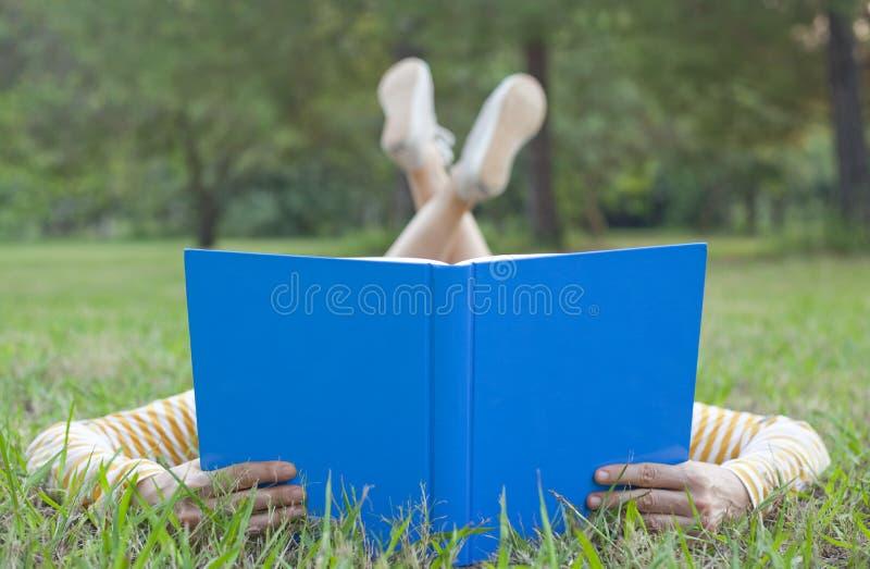 Flickaläsning bokar på gräs royaltyfri foto
