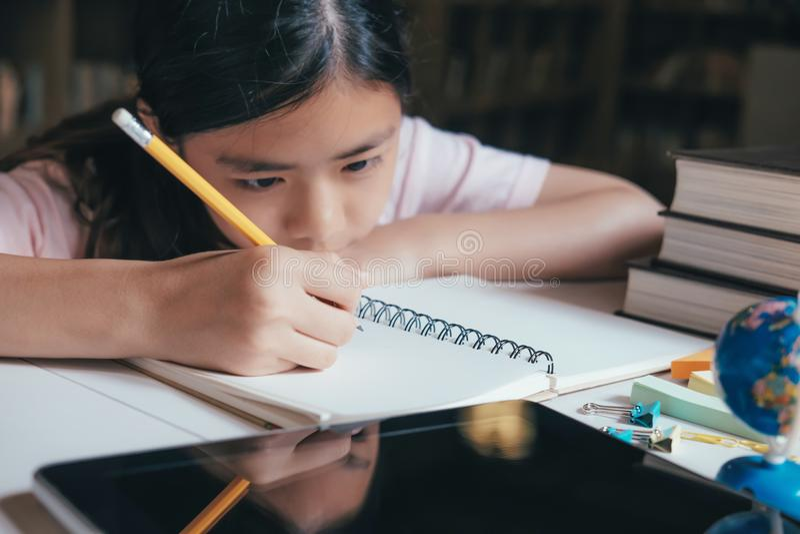 Flickaläsning och handstil och gör läxa i arkiv royaltyfria foton