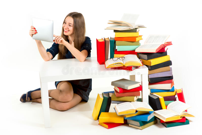 Flickaläsning på minnestavlan med högar av onödiga böcker arkivbilder