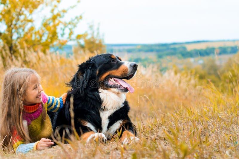 flickalögner bredvid stor hund på höst går arkivbilder