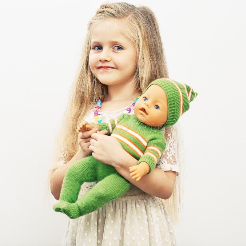 Flickalek med behandla som ett barn - dockan Fostrar dagbegrepp royaltyfri bild