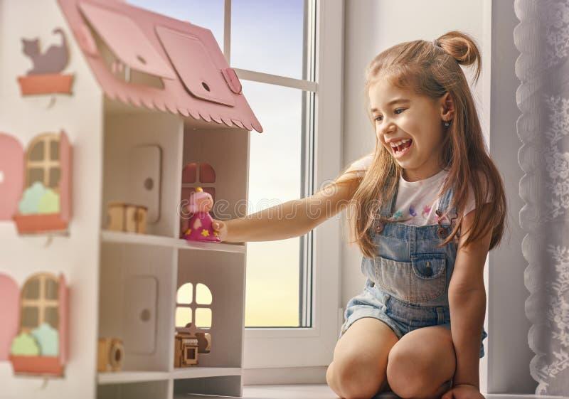 Flickalekar med dockhuset arkivfoton