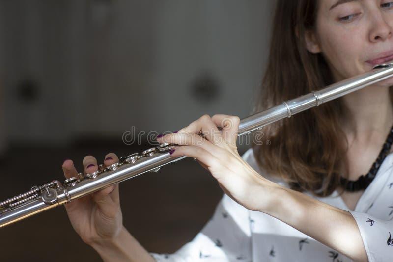 Flickalekar på flöjten Blåsa flöjt i händer av flickan under konserten Yrkesmässig musiker som spelar på flöjten arkivbild