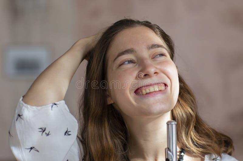 Flickalekar på flöjten Blåsa flöjt i händer av flickan under konserten Yrkesmässig musiker som spelar på flöjten arkivfoto