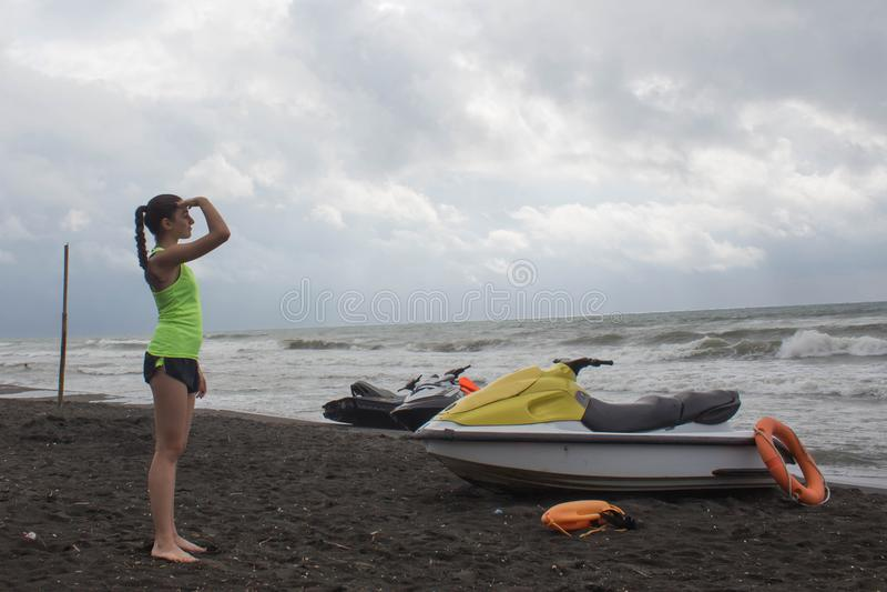 Flickalivräddare, med den orange bojet för liv som sparar det tjänstgörande förbise havet, havstrand Vattensparkcykel på stranden fotografering för bildbyråer