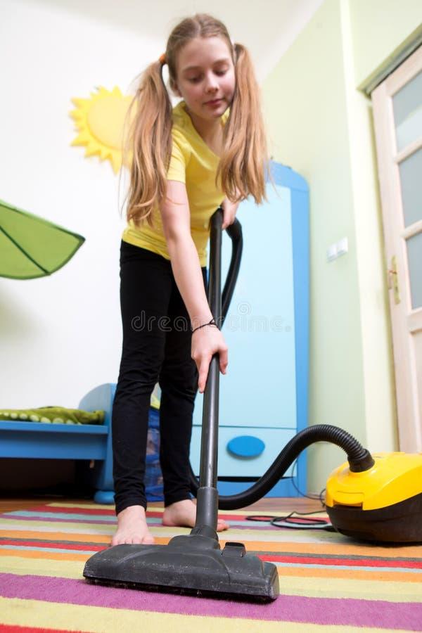 Flickalokalvårdgolv med dammsugaren royaltyfria foton