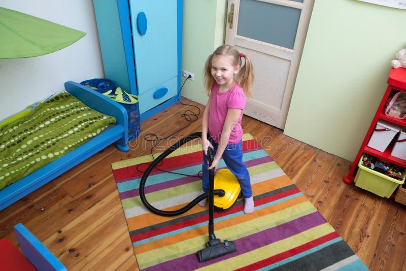 Flickalokalvårdgolv med dammsugaren arkivfoton