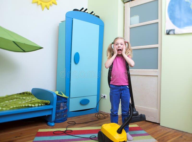Flickalokalvårdgolv med dammsugaren, fotografering för bildbyråer
