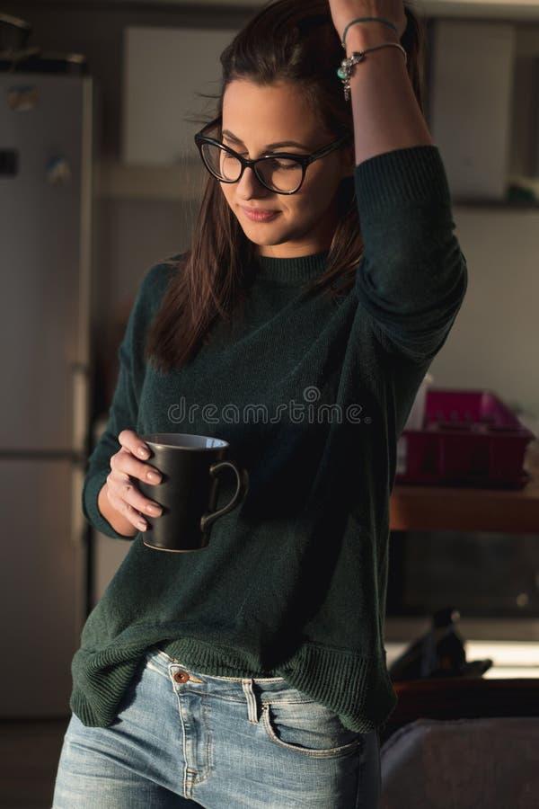 Flickalyftande hår upp och rymma kaffe i köket royaltyfria foton