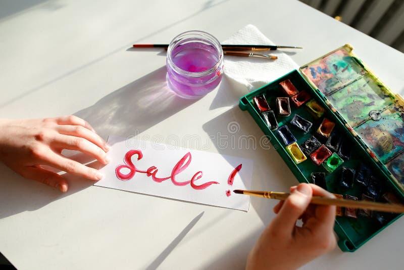 Flickamålaren skriver med borsten och målar inskriften på arket, royaltyfri foto