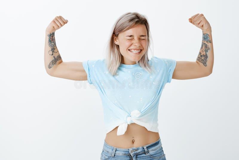 Flickamakt är den starkaste ståenden av glade snygga aktiva idrottskvinnor med ganska hår och tatuerade armar som visar royaltyfri foto