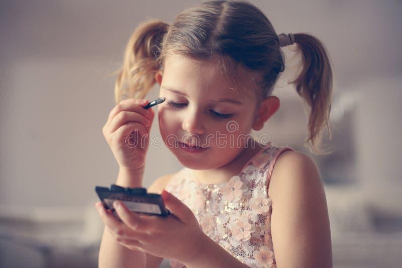 Flickamaterial Lilla flickan gör upp henne royaltyfria foton