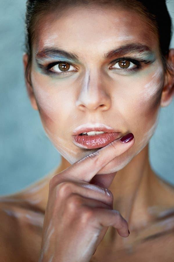 Flickamodell med idérik makeup, målarfärgslaglängder på framsidan idérik person Finger i munnen Se eftertänksam royaltyfria bilder