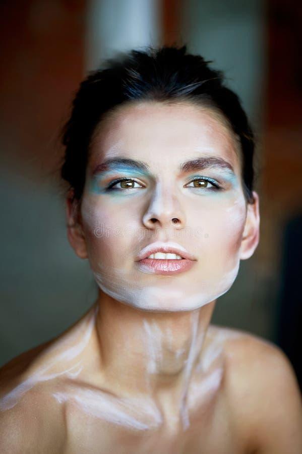 Flickamodell med idérik makeup, målarfärgslaglängder på framsidan idérik person strömförande skulptur Öppna ögon, kanter särade royaltyfria bilder