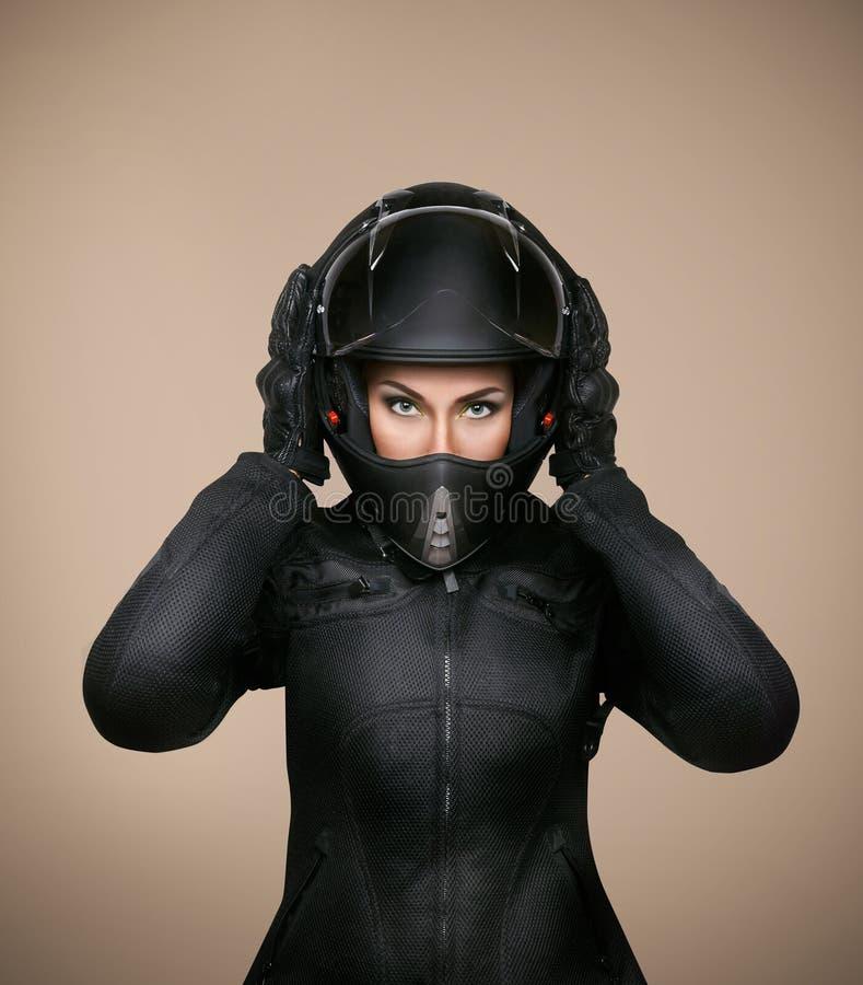 Flickamotorcyklist i ett svart omslag och en hjälm royaltyfria bilder