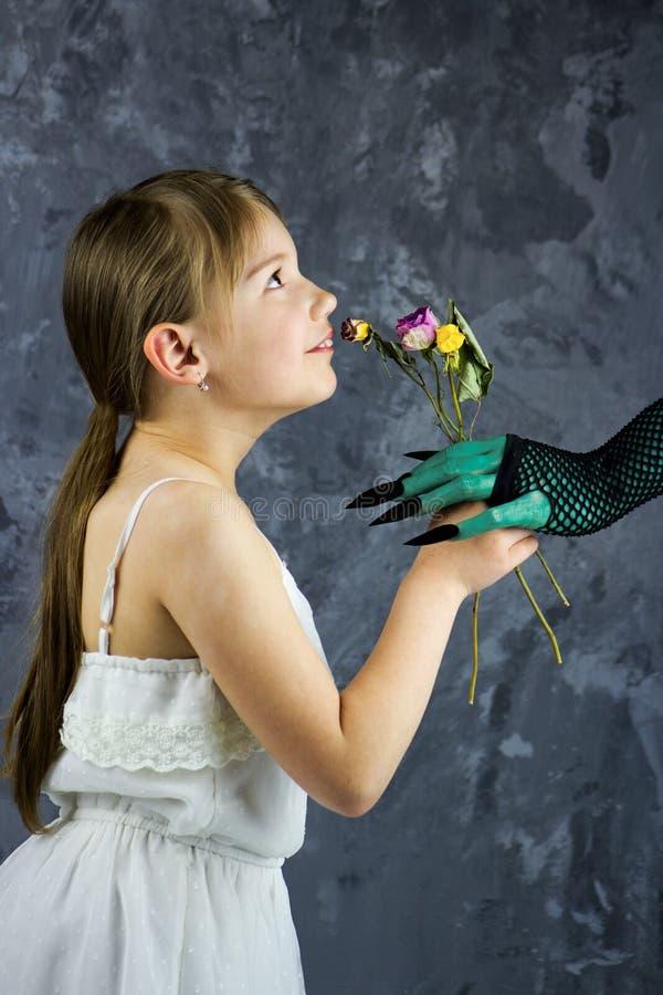 Flickan är att lukta av torra rosor Snövitsagan royaltyfri foto