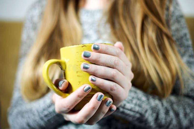 Flickan är den hållande koppen kaffe eller te i händer med grå färgsilvermanikyr royaltyfri foto