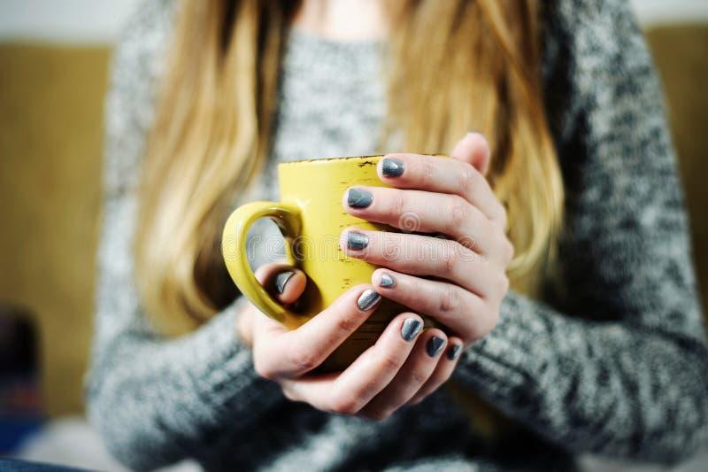 Flickan är den hållande koppen kaffe eller te i händer med grå färgsilvermanikyr royaltyfri bild