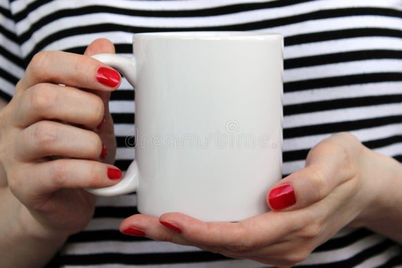 Flickan är den hållande vita koppen i händer
